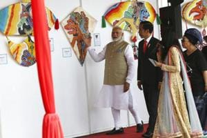 Indian Prime Minister Narendra Modi, left, talks with Indonesian President Joko Widodo, centre, at the National Monument Monas during India-Indonesia kite exhibition in Jakarta, Indonesia.