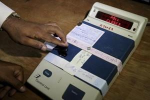 An election officer closes an electronic voting machine at the end of polls at a polling station in Bangalore.