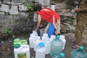 Residents wait to collect drinking water as the city faces water shortage in Shimla on May 31.
