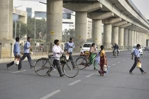 Pedestrians crossing a busy Golf Course Road, in Gurugram, India.