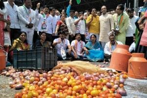 Farmers protest by spilling milk and vegetables at Khed Shivapur in Pune on Friday.