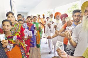 Voters showing their ID cards outside a polling booth during the bypoll at Lohian, Punjab, May 28, 2018 (Pardeep Pandit/HT)