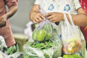 A lady buys vegetables in a plastic bag at a market in New Delhi's Bhogal on Monday.