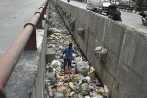 A man scavenges through a drain full of discarded plastic at Geeta colony in Delhi. As Delhi observes yet another World Environment Day, it is yet to get its act together when it comes to handling solid waste.