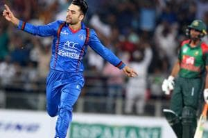 Afghan cricket player Rashid Khan (L) celebrates a wicket during the  Twenty20 International cricket match between Afghanistan and Bangladesh at Rajiv Ghandi International Cricket Stadium in Dehradun.
