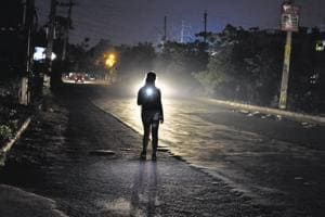 A resident of Sector 38 lights up her mobile flashlight. The area is in dire need of functional street lights as 60% of them are non-functional.