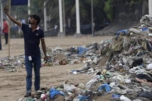 A man takes a selfie in front of a heap of garbage on the shores of the Arabian Sea in Mumbai.
