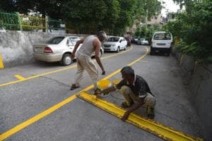 A labourer paints a line on a road for making a boundary for parking at Lajpat Nagar II in New Delhi , India, on Monday, June 11, 2018.