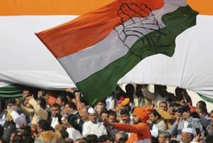 A Congress party worker waves the party flag during a function.