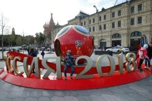 People gather near decorations for the upcoming FIFA World Cup 2018, with St. Basil