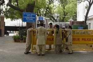 Police wait outside the L-G House in New Delhi.