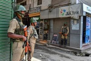 CRPF personnel stand guard near a shop on the first day of Ramzan, in Srinagar.
