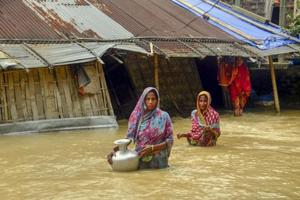 Villagers carry clean water as they wade across flood-affected areas at Nilambazar village, in Karimganj on Sunday.