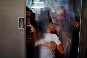 Relatives of a Palestinian, who was killed at the Israel-Gaza border, react at a hospital in Gaza City June 18, 2018.