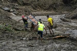 People engaged in rescue work after a landslide in Kattippara in Kozhikode on June 14, 2018.