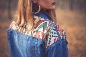 A model wears a denim jacket with geometric detailing.