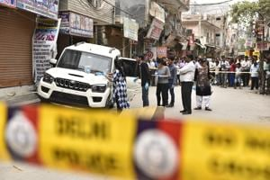 Forensic experts investigate the car of one of the gangs involved in a gunbattle in North Delhi
