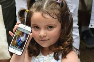 Luciana Villavicencio age 4, holds up a photo of her family on a cellphone during a press conference on June 18, 2018 regarding her father Pablo Villavicencio, an Ecuadorean, who was detained by Immigration and Customs Enforcement despite being in the process of adjusting his immigration status. His wife and two daughters are all US citizens.