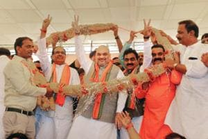 BJP President Amit Shah, flanked by Madhya Pradesh Chief Minister Shivraj Singh Chauhan (L) and BJP state chief Rakesh Singh being garlanded by party workers in Jabalpur on June 12, 2018.