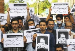 Journalists of Rising Kashmir joined by other journalists from various media hold placards during sit-in protest against the killing of Shujaat Bukhari at Lal Chowk, in Srinagar, on June 18, 2018.