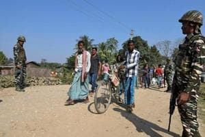 Villagers walk past Central Reserve Police Force personnel patrolling a road ahead of the publication of the first draft of the National Register of Citizens in the Juria village of Nagaon district in Assam, in 2017.