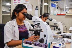 Paramedical staff are seen working in the microbiology lab in Bharati Hospital.