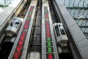 Elevators travel next to electronic boards displaying stock figures at the National Stock Exchange of India Ltd. (NSE) building in Mumbai.