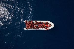 Refugees and migrants wait to be rescued by members of the Spanish NGO Proactiva Open Arms, after leaving Libya trying to reach European soil aboard an overcrowded rubber boat, north of Libyan coast, Sunday, May 6, 2018.