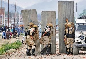 Police take guard behind a barricade as Kashmiri protesters clash with police on the outskirts of Srinagar after forces killed four militants at Nowshera village in South Kashmir on June 22, 2018