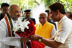 BJP state chief Subhash Barala (right) welcoming party national president Amit Shah as Haryana CM Manohar Lal Khattar looks on, at Haryana Bhawan in New Delhi on Friday.
