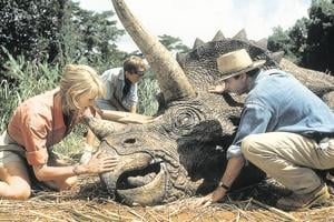 Laura Dern and Sam Neill come to the aid of a Triceratops in a scene from the first Jurassic Park film.