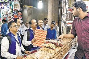 BMC inspectors speak to a shopkeeper in Mumbai on Saturday.