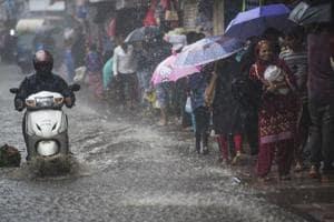 A biker drives through a waterlogged road at Dadar in Mumbai on Saturday.