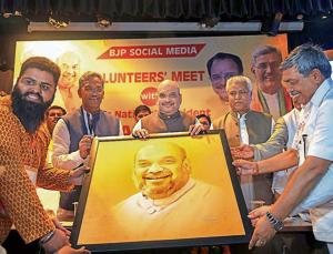 BJP social media volunteers offer a portrait to party president Amit Shah at a meeting in Dehradun.