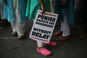 A protestor stands with a placard during a protest against two recently reported rape cases as they gather near the parliament in New Delhi.