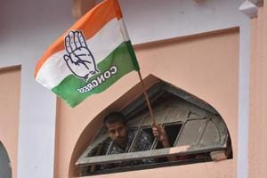 Congress supporter waves party flag during the road show of the All India Congress Committee President Rahul Gandhi.