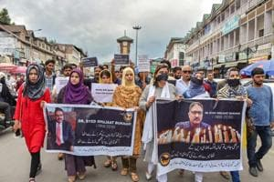 Journalists hold placards during a silent protest march against the killing of Rising Kashmir newspaper editor-in-chief Shujaat Bukhari, in Srinagar on June 26, 2018.