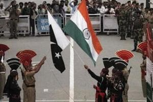 Pakistani rangers (wearing black uniforms) and Indian Border Security Force (BSF) officers lower their national flags during a daily parade at the Pakistan-India joint check-post at Wagah border, near Lahore November 3, 2014.