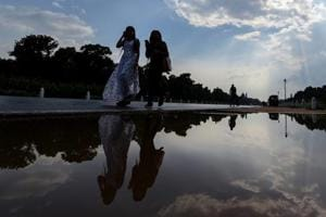 Women walk past a puddle of water at Rajpath after a short spell of rain in New Delhi on Thursday. Pre-monsoon showers hit the capital this week, with light rain on Monday and Tuesday and heavier showers on Wednesday.
