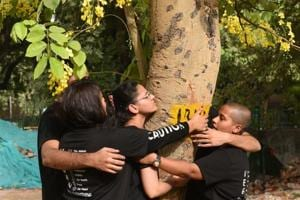 People hug a tree as they protest against the cutting of trees at Sarojini Nagar in New Delhi, India, on Sunday, June 24, 2018.