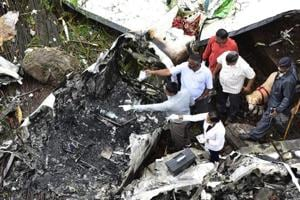 Forensic experts examine the debris of a Beechcraft King Air C90 turboprop aircraft that crashed in Old Malik Estate in Ghatkopar, Mumbai, on June 28, 2018.