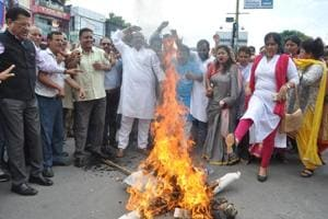 Congress workers burn an effigy of the Uttarakhand government in Dehradun on Saturday to protest suspension of a woman schoolteacher.