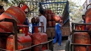 Workers load liquefied petroleum gas (LPG) cooking cylinders onto a supply truck outside a distribution centre in Mumbai, India, February 19, 2015.