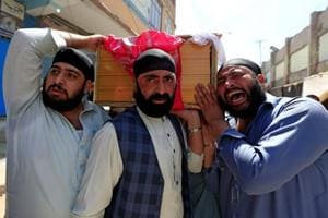 Afghan Sikh men carry the coffin of a victim of the suicide terror attack in Jalalabad city, Afghanistan, on July 2, 2018.