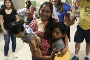 Buena Ventura Martin-Godinez, center, holds her son Pedro, left, as she is reunited with her daughter Janne, right, at Miami International Airport, Sunday, July 1, 2018, in Miami.