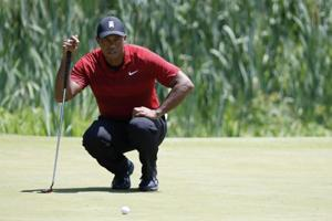 Tiger Woods of the United States lines up a birdie putt on the third hole during the final round of The National golf tournament at TPC Potomac at Avenel Farm.