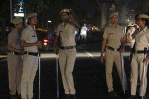 Women police personnel stand guard at a dark strech of road between MG Road and Sikanderpur metro stations.