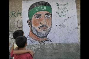 Kashmiri children look at a graffiti of Burhan Wani, a top Militant commander who was killed in an encounter, during curfew in Srinagar, in August 2016. Wani's death stoked months of unrest in the Kashmir Valley in 2016.