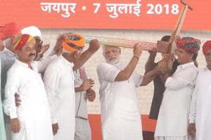 Prime Minister Narendra Modi being presented a plough from farmers as he meets beneficiaries of governemnt schemes at Amrudon Ka Bagh in Jaipur.