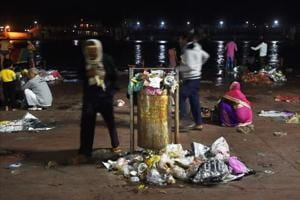 A Ganga ghaat is left littered with clothes, plastic sheets and other garbage.